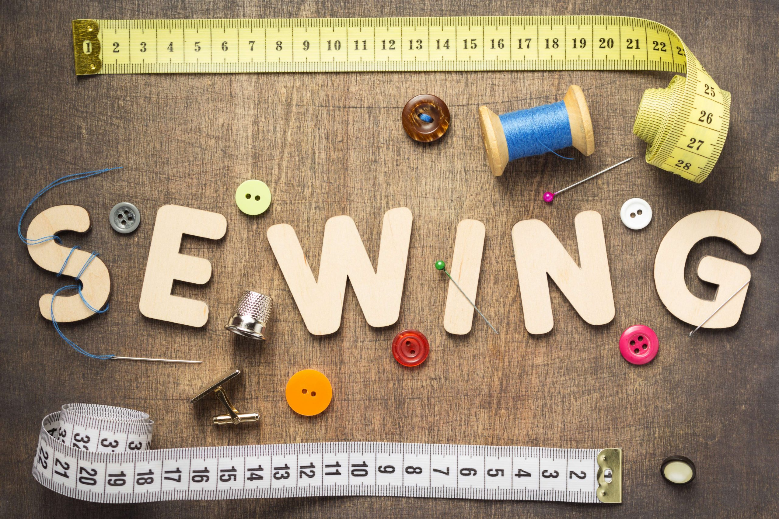 Image of needle, thread, measuring tape, and buttons