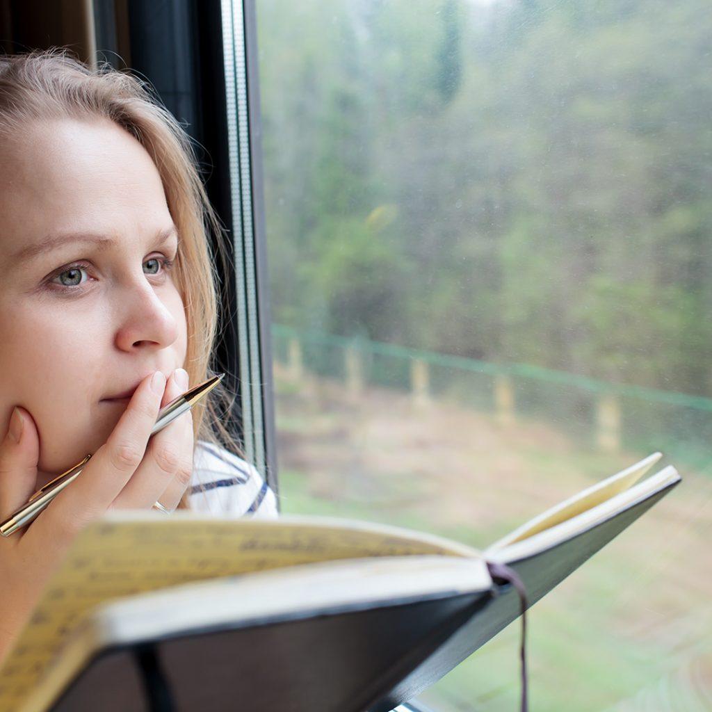 woman writing at window